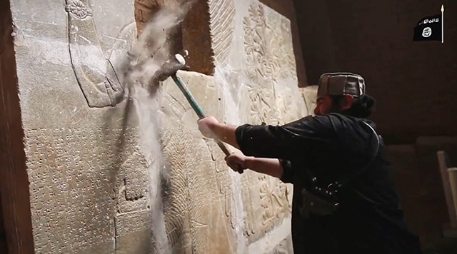 An Islamic State militant participates in the destruction of ancient ruins near the city of Nimrod, Iraq, in a video released by the Islamic State.