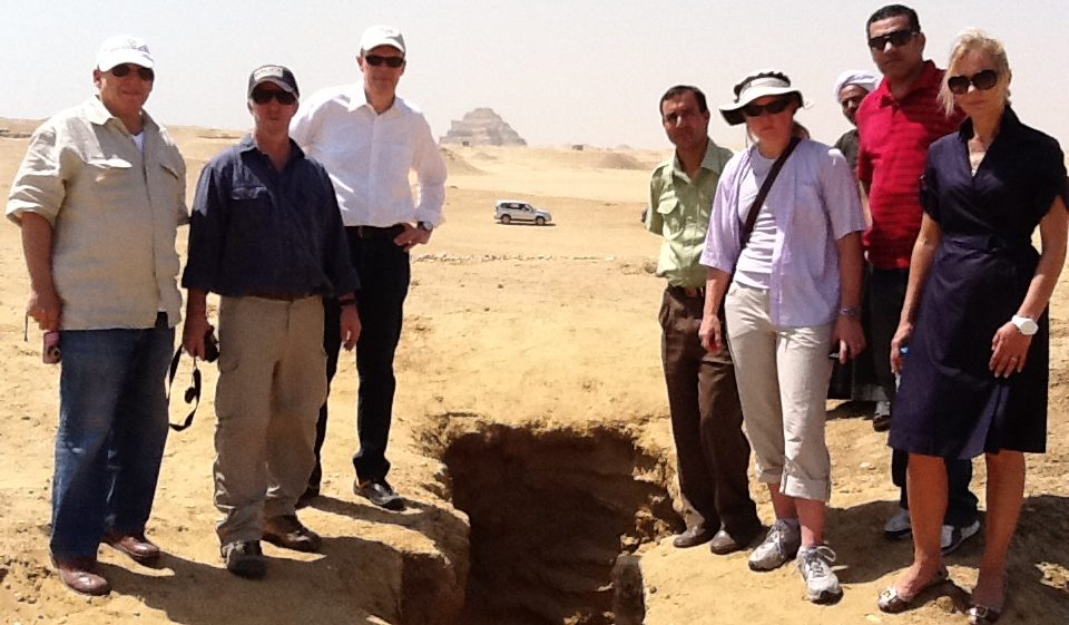 ICPEA members (from left) Ted Greenberg, Eric Cline, Peter Herdrich, driver, Sarah Parcak, security, and Deborah Lehr examine a looters pit in Saqqara. Copyright Peter Herdrich