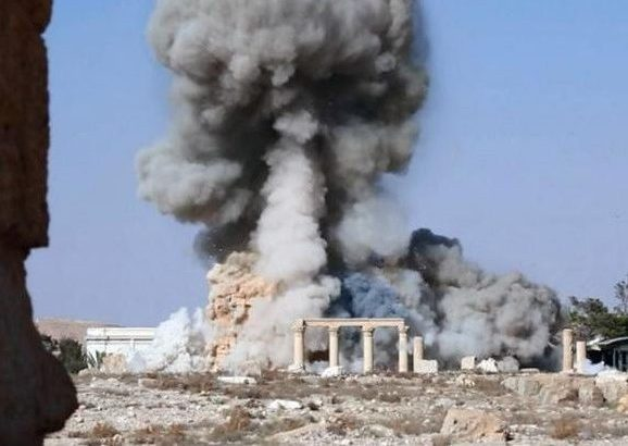 This undated photo released Tuesday, Aug. 25, 2015 on a social media site used by Islamic State militants, which has been verified and is consistent with other AP reporting, shows smoke from the detonation of the 2,000-year-old temple of Baalshamin in Syria's ancient caravan city of Palmyra. A resident of the city said the temple was destroyed on Sunday, a month after the group's militants booby-trapped it with explosives. Arabic at bottom reads,